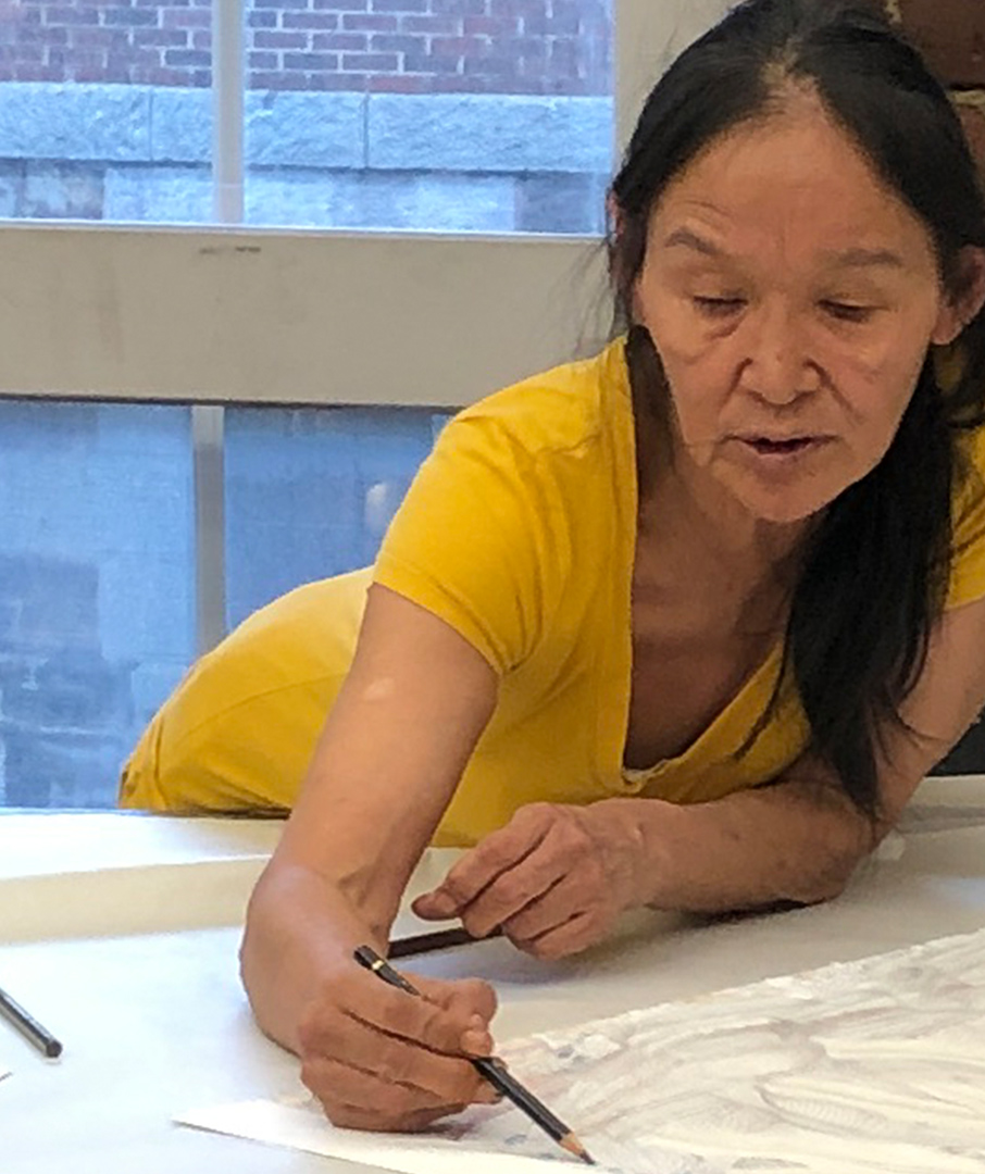Colour photograph of artist Shuvinai Ashoona in a yellow t-shirt bent over a table drawing on paper in brown pencil crayon. A window is behind her where you see a neighbouring brick building.