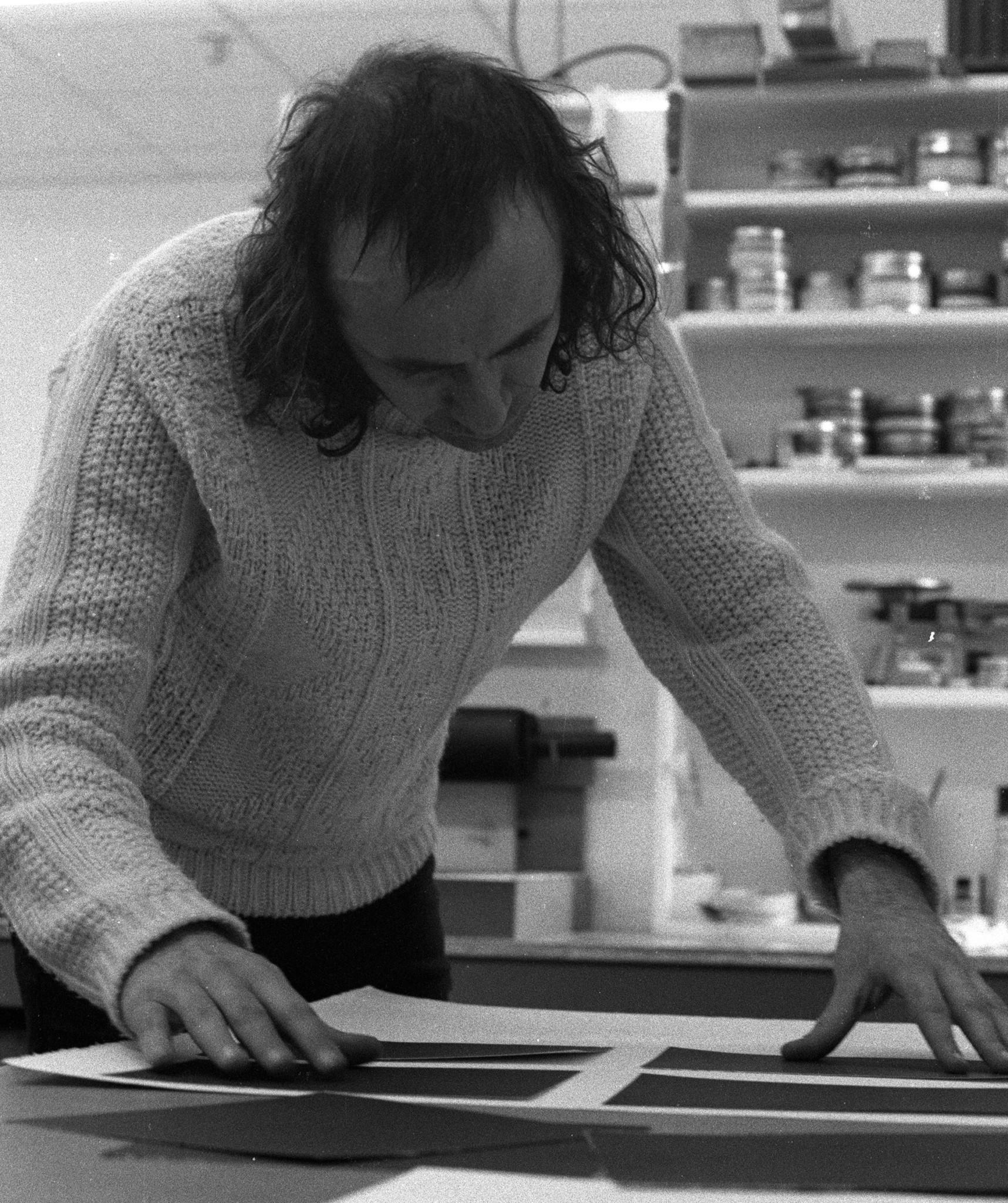 Black and white photo of artist Vito Acconci, with shoulder length hair wearing a cable knit sweater adjusting prints in the print studio. A shelf of inks and chemicals is behind him.